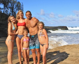 Family with mother, father and three daughters posing on a secluded beach
