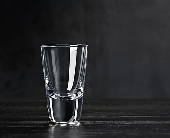 A clear shot glass on a dark wooden surface with a black background