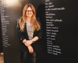 Woman standing in front of a blackboard with a long list written on it