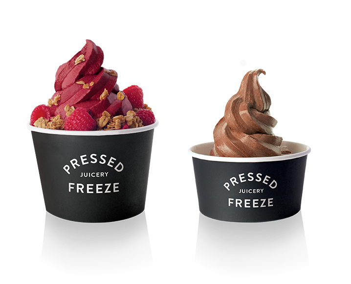 Two Pressed Juicery Freeze containers, one large raspberry flavor with fresh raspberries and granola on the left, and a smaller chocolate one on the right
