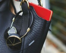 Close-up of a pair of black and gold headphones hanging out of a black leather purse with a red book sticking out of the bag