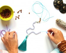 Hands making a mala with beads, string, tassel and other items