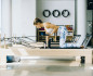 Woman in workout clothes performing Pilates reformer exercises