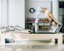 Woman performing Pilates reformer exercises inside a studio