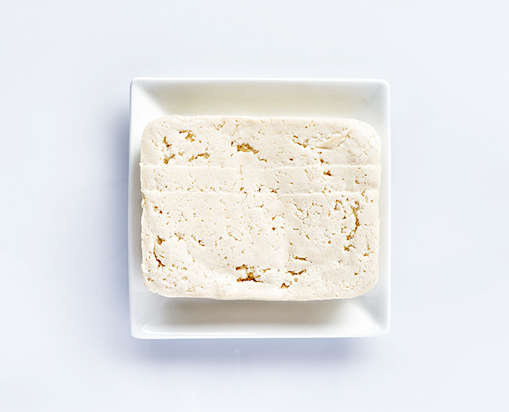 An aerial shot of a white plate with a block of tofu