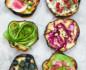 Aerial close-up of 6 varying styles of eggplant toast placed in 2 vertical columns