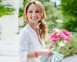 Giada De Laurentiis holding a jar full of flowers on a blurred garden background