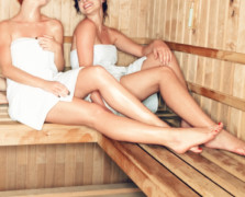 Two women on a wooden bench inside a sauna of a Korean spa