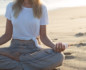 Woman's body from the neck down in meditation pose holding a selenite crystal