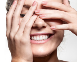 girl with hands in front of face smiling