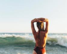 woman in bathing suit facing the ocean