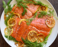 Aerial view of a white plate with grilled wild salmon, lemon slices and dill