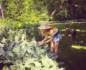 Carson Meyer in her Malibu garden, wearing a sun hat, attending to her plants