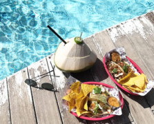 A wooden planked poolside with black sunglasses, a green coconut drink and two pink baskets with tacos and tortilla chips