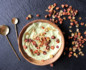 Wooden bowl of mashed potatoes sprinkled with flakes of dehydrated carrot chips, with two copper spoons on the left