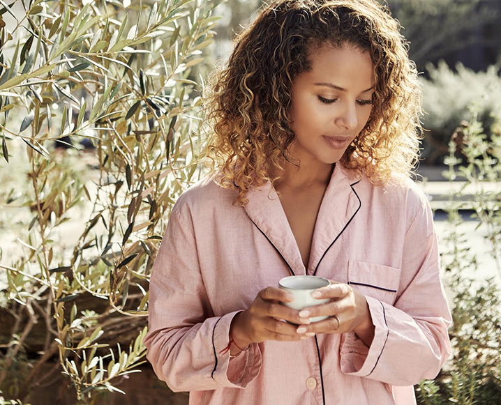 Denise Vasi wearing pajamas and holding a coffee cup in an outdoors background
