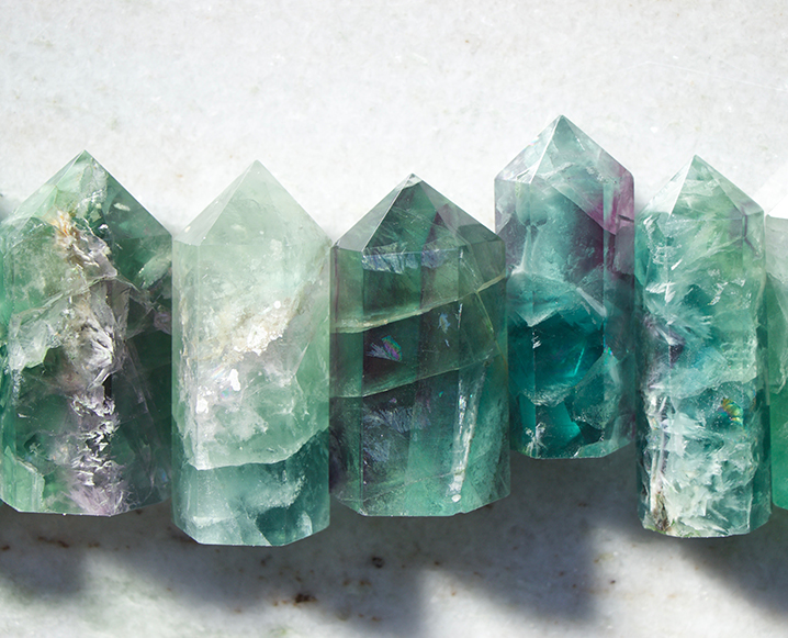 Five pieces of fluorite crystal stacked next to each other on a marble surface